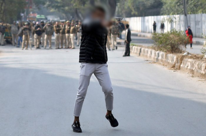 An unidentified man brandishes a gun during a protest against a new citizenship law outside the Jamia Millia Islamia university. (Reuters Photo)