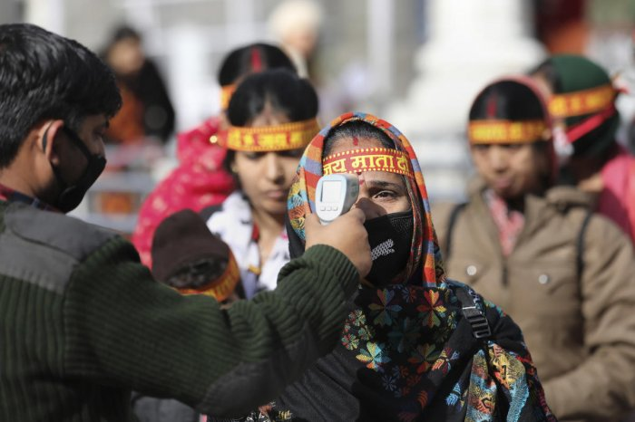 An official uses a thermal screening device on devotees to mitigate the coronavirus pandemic, at Vaishno Devi in Jammu, Friday, March 13, 2020. (PTI Photo)