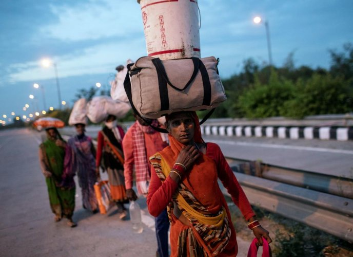 Migrant workers carry their belongings as they walk along a road to return to their villages, during a 21-day nationwide lockdown to limit the spreading of coronavirus disease, in New Delhi. Credit: Reuters Photo