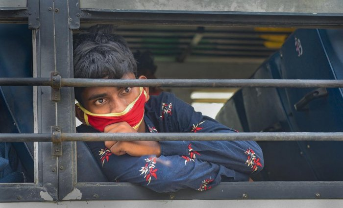 A migrant worker wearing a mask looks through a window of a bus to reach his native place, during the ongoing nationwide COVID-19 lockdown, in Kolkata, Wednesday, April 29, 2020. (PTI Photo)