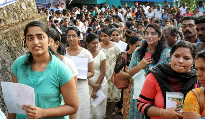 Applicants wait outside an examination centre to appear in the NEET 2018 test conducted by CBSE in Kochi on Sunday. PTI/FILE
