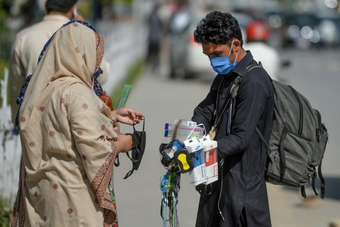 A street vendor (R) wearing a facemask as a preventive measure against the COVID-19 coronavirus, interacts with customers alongside a street in Islamabad on March 19, 2020. Credit: AFP Photo