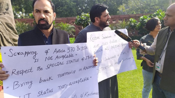 """Holding placards against the abrogation of the provisions of Article 370, the two MPs urged the government to """"respect"""" the special status of the region. DH Photo"""