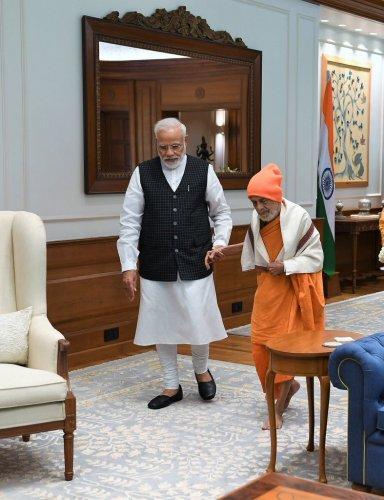 PM Modi and Pejawar seer Vishwesha Theertha. (Twitter @narendramodi)