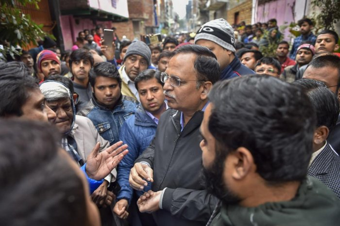 Delhi Health Minister Satyendar Jain interacts with the residents, where a fire broke out in a three-storey residential-cum-commercial building, in outer Delhi's Kirari area, Monday, Dec. 23, 2019. At least nine people, including three children, were killed in the incident. (PTI Photo/Ravi Choudhary)