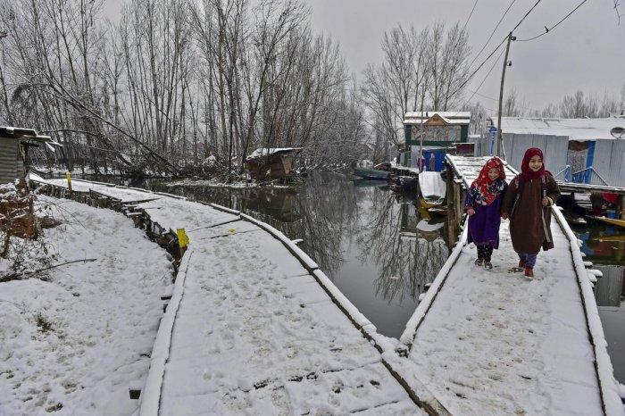 Young girls walk over a snow-laden wooden bridge after a light snowfall, in Srinagar. PTI