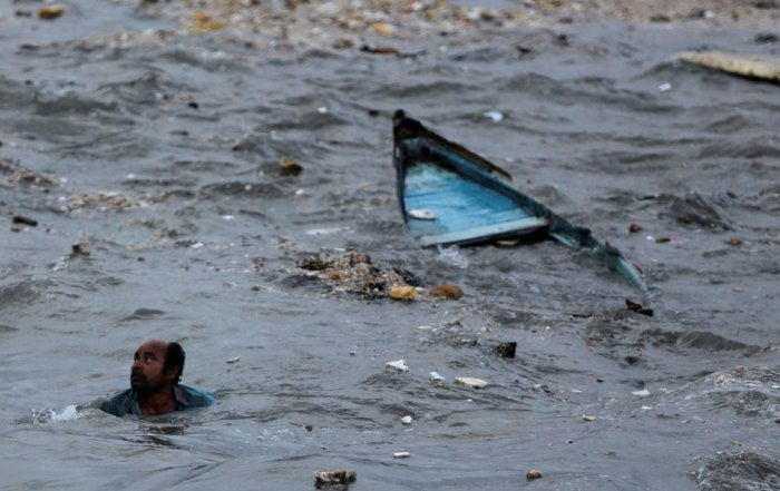 A fisherman swims to shore after his boat capsized due to high waves ahead of the expected landfall of Cyclone Vayu at Veraval, India, June 12, 2019. REUTERS/Amit Dave