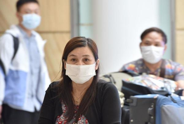 Passangers arrive at Sydney airport wearing masks after landing on January 25, 2020. (AFP Photo)