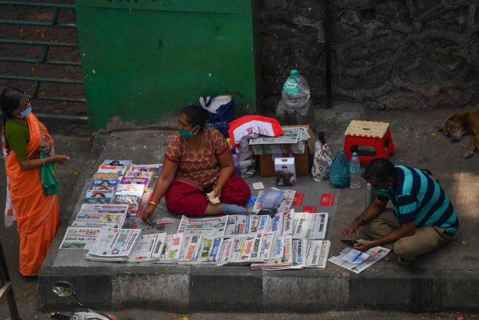 A woman selling newspapers interacts with a customer during a government-imposed nationwide lockdown as a preventive measure against the spread of the COVID-19 coronavirus in Mumbai on April 27, 2020. Credit: AFP Photo