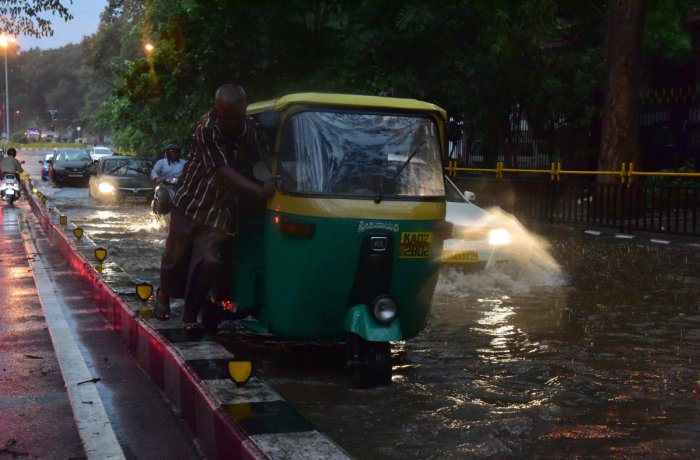 An autorickshaw driver struggles to push his vehicle along a waterlogged Ambedkar Veedhi near KR Circle on Friday. DH photo/IRSHAD MAHAMMAD
