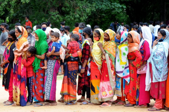 Women migrant workers stand in a queue for food and water at Palace Grounds in Bengaluru. DH File Photo