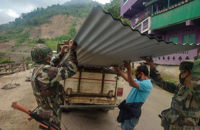 Assam Rifles personnel unload tin-sheets from a van for construction of quarantine facility at Kisama heritage village in Kohima. PTI