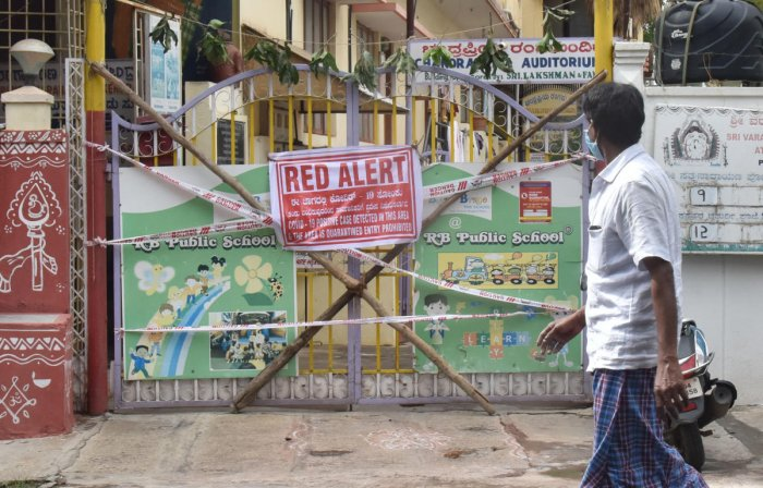 A man walks in front of sealed down area in Sanjaynagar, Bengaluru, on Friday. DH Photo/ Janardhan B K