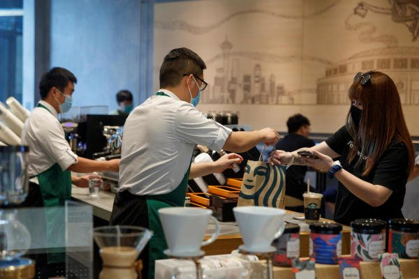 A staff member serves a customer at a Starbucks Coffee house in Beijing, China. Credit: Reuters