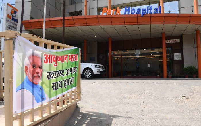A banner for Ayushman Bharat healthcare scheme, is pictured at a gate at Park Hospital in Gurgaon. Credit: AFP Photo