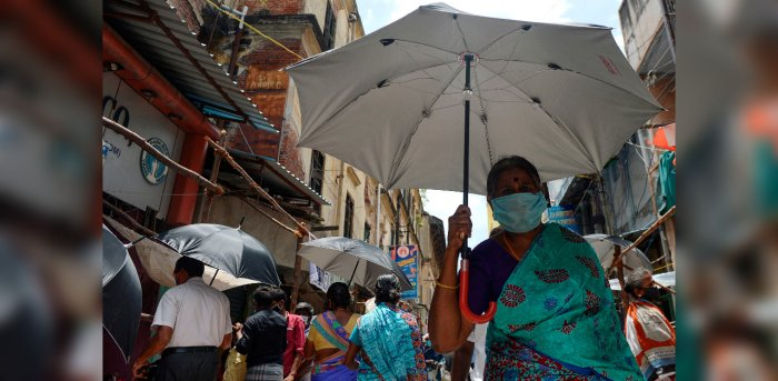 People hold umbrellas distributed by volunteers to maintain social distancing as a preventive measure against the COVID-19 coronavirus, at a market in Chennai. Credit: AFP