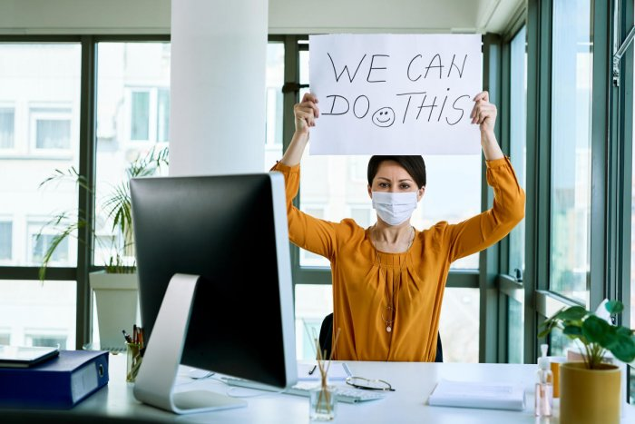 Businesswoman holding placard with we can do this text as support during virus epidemic.Upskilling and career change are two options trending among young professionals