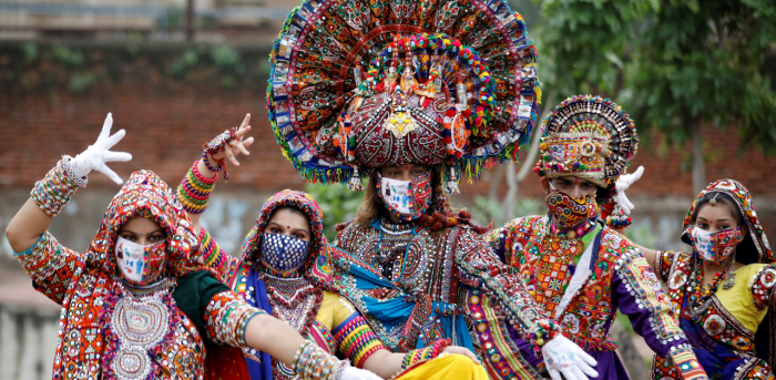 Participants in traditional costumes wearing face masks pose for a picture during rehearsals for Garba amid Covid-19. Credit: Reuters Photo