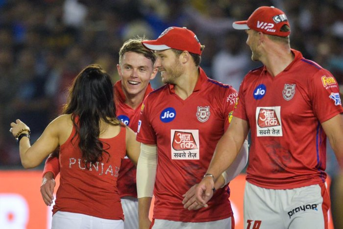 Kings XI Punjab's bowler Sam Curran (left) celebrates with his team owner Preity Zinta and team-mates after their win over Delhi Capitals in Mohali on Monday. AFP