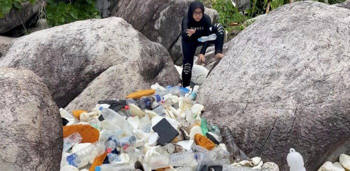A woman clears trash by the sea at Tioman Island, Pahang, Malaysia. Credit: Reuters