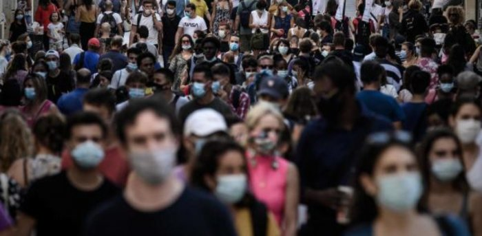 Pedestrians, some of them wearing protective face masks due to the Covid-19 coronavirus pandemic, walk in a street lined with shops in Bordeaux, southwestern France. Credit: AFP Photo