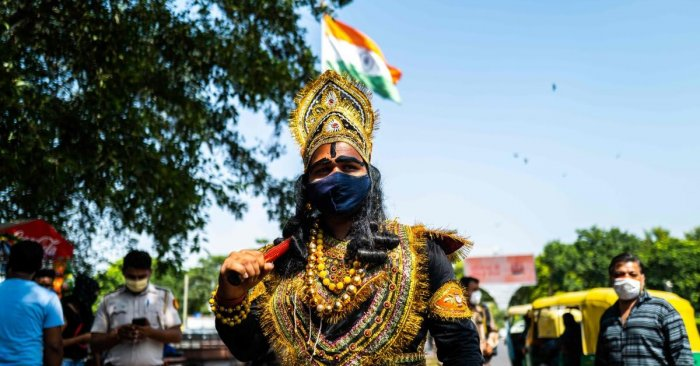 An officer from the District Magistrate Office dressed as Hindu lord of death and justice, Yamraj (C), looks for people not wearing facemasks as a preventive measure against the Covid-19 coronavirus in a public place in New Delhi on September 28, 2020. Credit: PTI Photo