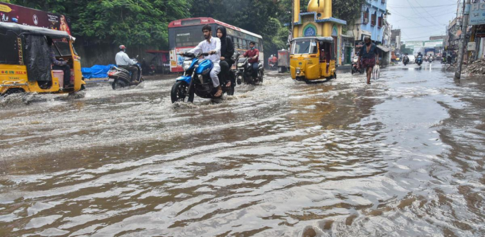 Vehicles ply on a waterlogged street, following continous heavy rainfall, in Hyderabad. Credit: PTI Photo
