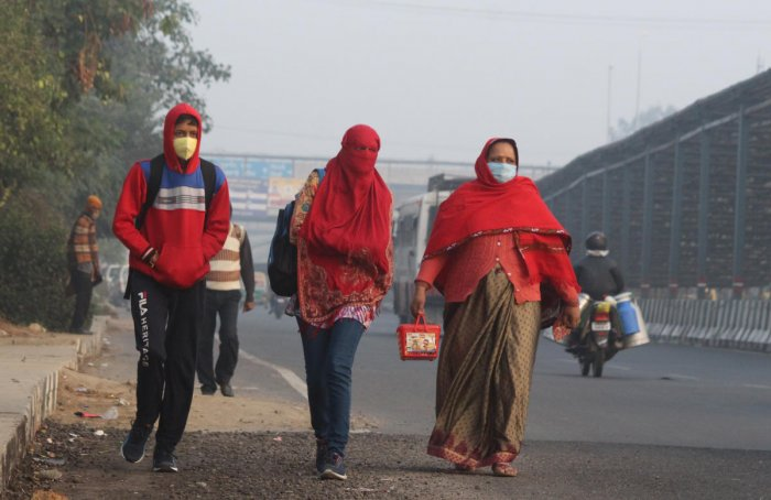 People wearing warm clothes walk along a road, in Gurugram. Credit: PTI
