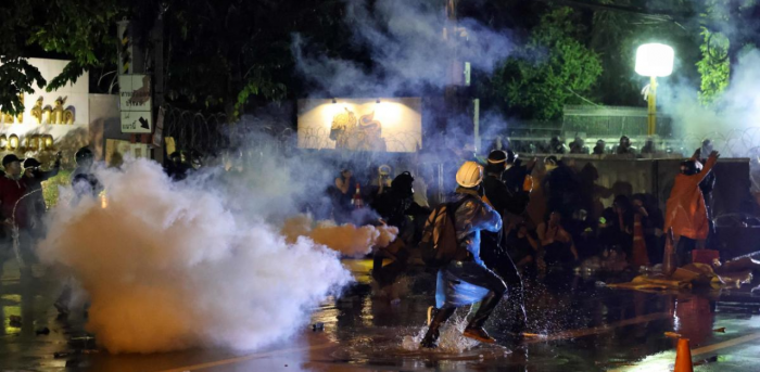 Pro-democracy protesters react as police fire tear gas during an anti-government rally near the Thai Parliament in Bangkok. Credit: Reuters Photo