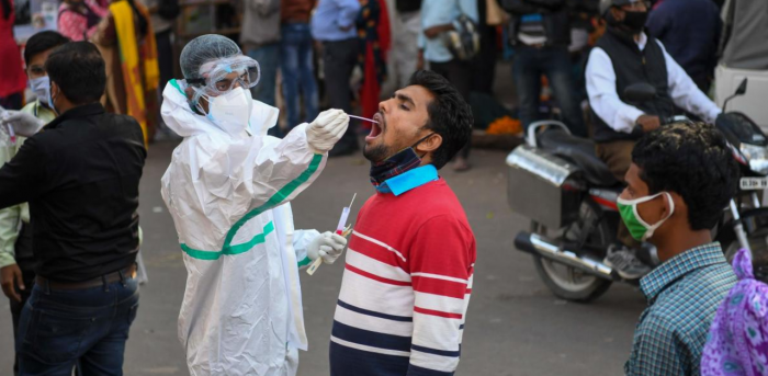 A medical worker collects a swab sample from a man for a RT-PCR test for the Covid-19 coronavirus along a street in New Delhi. Credit: AFP Photo