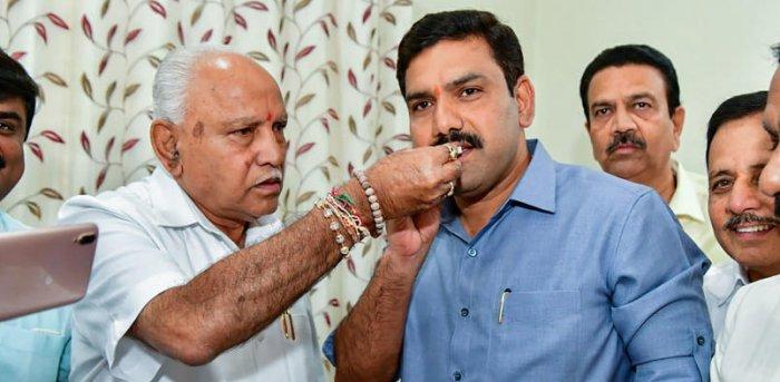Karnataka Chief Minister BS Yediyurappa offer sweets to son BY Vijayendra. Credit: PTI file photo
