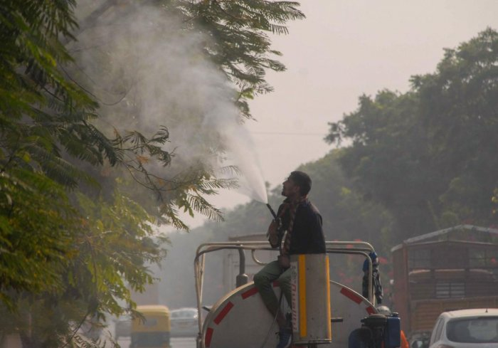 A worker sprays water on trees to curb dust pollution, in Noida. Credit: PTI