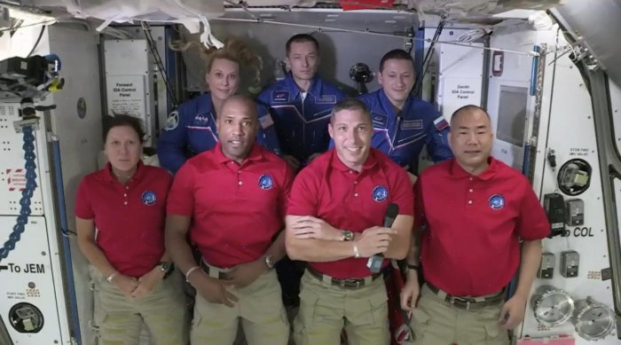 In this frame grab from NASA TV, SpaceX Dragon crew, from front left to right, Shannon Walker, Victor Glover, Mike Hopkins and Soichi Noguchi stand with International Space Station crew Kate Rubins, from back left, Expedition 64 commander Sergey Ryzhikov and Sergey Kud-Sverchkov. Credit: AP