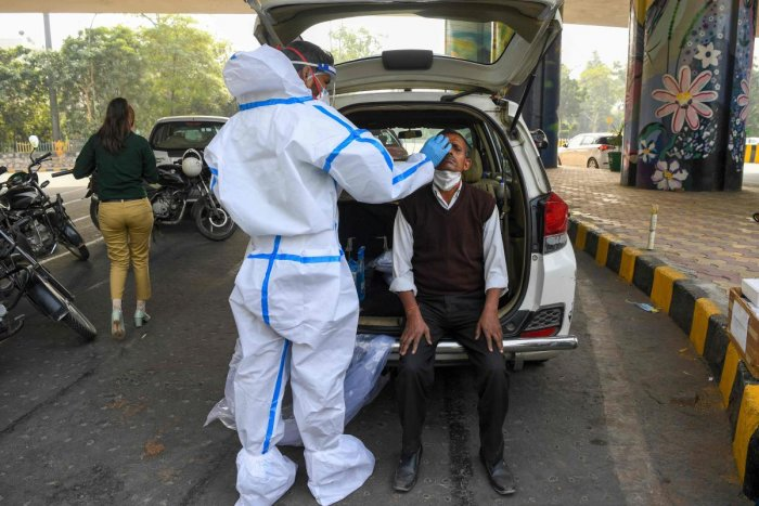 A medical worker wearing protective gear collects a nasal swab sample from a man for a Rapid Antigen Test (RAT) for the Covid-19 coronavirus as Noida authorities started conducting random coronavirus testing on commuters arriving from Delhi at Delhi-Uttar Pradesh state border in Noida. Credit: AFP