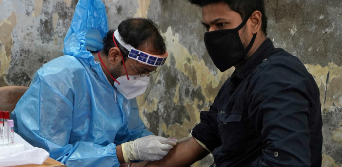 A healthcare worker wearing a protective gear collects blood sample from a man, who has recovered from the coronavirus disease (COVID-19), during a plasma donation camp inside a classroom at a slum in Mumbai, India, July 24, 2020. Credit: Reuters Photo