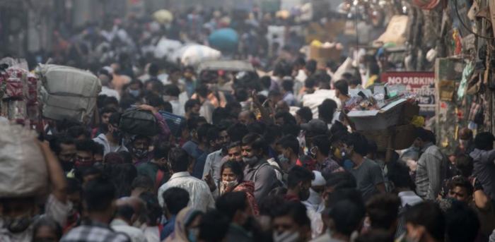 People walk along a street of a market area amid the Covid-19 coronavirus pandemic in New Delhi on November 7, 2020. Credit: AFP Photo
