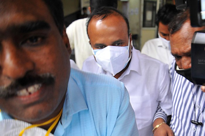 Former mayor R Sampath Raj (wearing a white facemask) upon his arrest in Bengaluru on Tuesday. DH PHOTO/PUSHKAR V