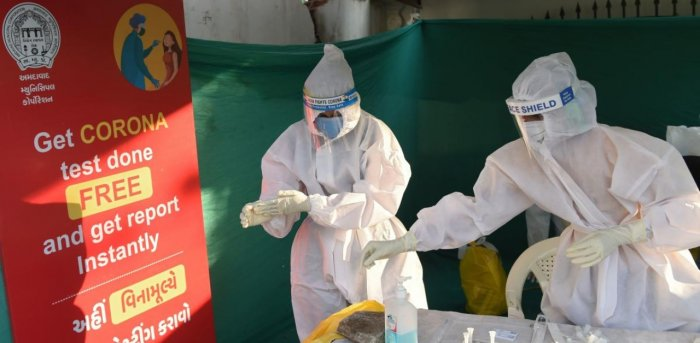 Health workers prepare to take swab sample from residents to test for the Covid-19. Credit: AFP Photo