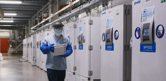 A worker passes a line of freezers holding coronavirus disease vaccine candidate BNT162b2 at a Pfizer facility in Puurs, Belgium. Credit: Reuters Photo