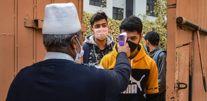 Students undergo thermal screening as they arrive to appear in class 10th examination, at a school in Srinagar. Credit: PTI Photo