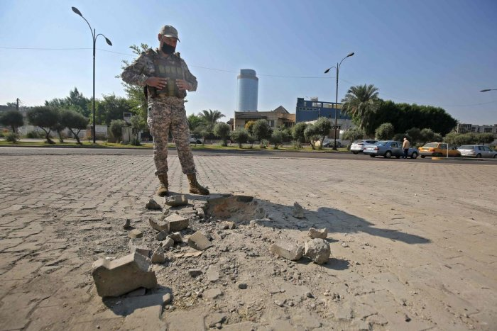 A member of the Iraqi security forces inspects the damage outside the Zawraa park in the capital Baghdad on November 18, 2020, after volley of rockets slammed into the Iraqi capital breaking a month-long truce on attacks against the US embassy. Credit: AFP