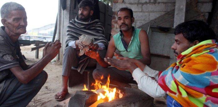People sit around a bonfire to warm themselves, near Rajiv Chowk in Gurugram. Credit: PTI.