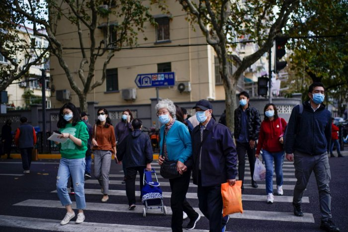 People wearing face masks are seen on a street amid the global outbreak of the coronavirus disease in Shanghai. Credit: Reuters