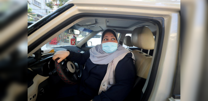 Palestinian woman Naela Abu Jibba, who started a women-only taxi service in Gaza Strip, sits behind the wheel of her vehicle at Beach refugee camp in Gaza City November 17, 2020. Picture taken November 17, 2020. Credit: Reuters Photo