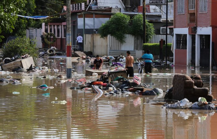 A man salvages belongings in the flooded municipality of La Lima near San Pedro Sula in Honduras, on November 19, 2020, after heavy rains from Hurricane Iota caused the Chamelecon river to overflow. - Iota's death toll rose to 38 on Wednesday after the year's biggest Atlantic storm unleashed mudslides, tore apart buildings and left thousands homeless across Central America, revisiting areas devastated by another hurricane just two weeks ago. Credit: AFP Photo