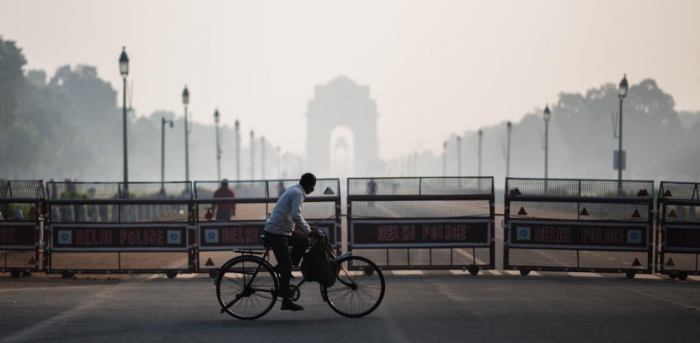 A man rides a bicycle along a street amid smoggy conditions in New Delhi. Credit: AFP Photo