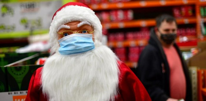 A shopper walks past a Santa Claus effigy wearing a face mask due to Covid-19 at a Home Depot store in Wilmington, Delaware. Credit: Reuters Photo