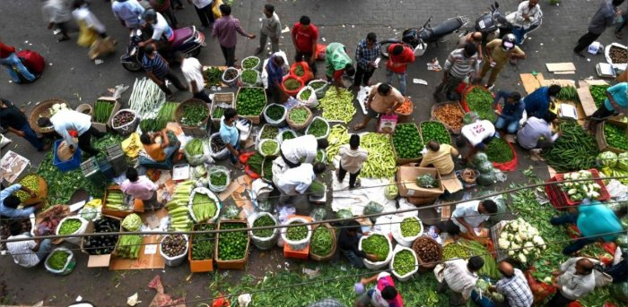 People gather to shop at an open air vegetable market early in the morning in Mumbai. Credit: AFP Photo