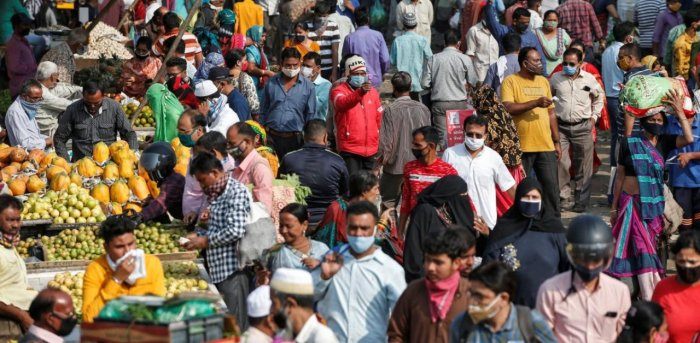 A health worker takes the temperature of shoppers at a crowded market amid the spread of the coronavirus disease in Ahmedabad. Credit: Reuters Photo