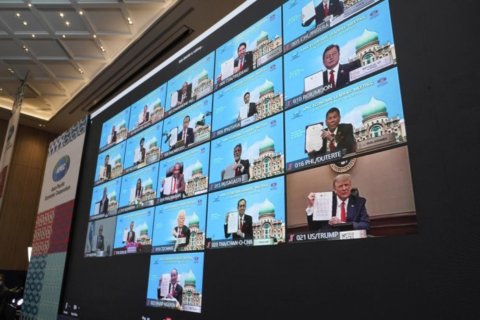 Monitors showing US President Donald Trump, right bottom, hold up declaration together with other leaders attending the first virtual Asia-Pacific Economic Cooperation (APEC) leaders' summit, hosted by Malaysia. Credit: AP/PTI.